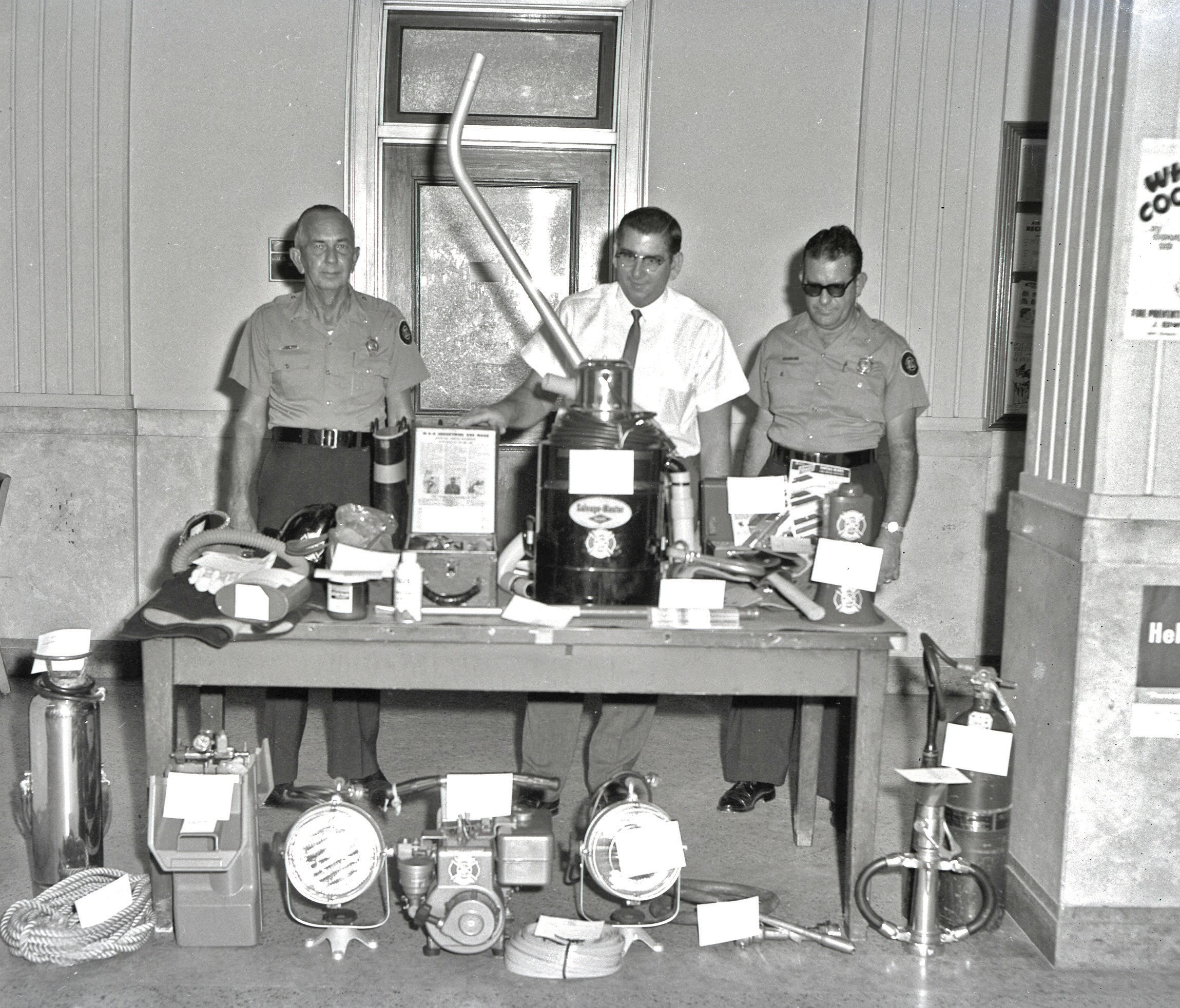 "A fire safety display at the Key West Post Office. From left, assistant Chief Johnny Roberts, Elio Bello of the post office and Chief Joseph ""Bum"" Farto, circa 1964."