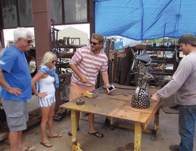 Derek Arnold demonstrates his metallic sculpture.